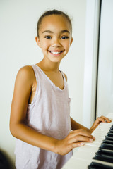 Smiling Mixed Race girl playing music on keyboard