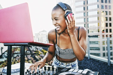 Female DJ with headphones enjoying music on rooftop party