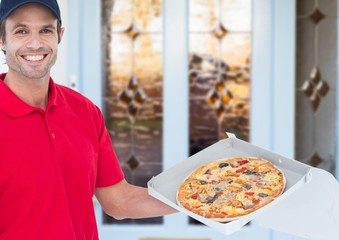 Happy deliveryman in the door of the house showing the pizza