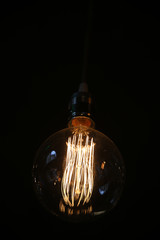 Closeup pf an antique vintage edison style light bulb against dark background