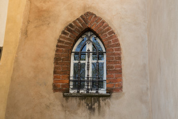 Brick framed arched window in old village in Northern Italy