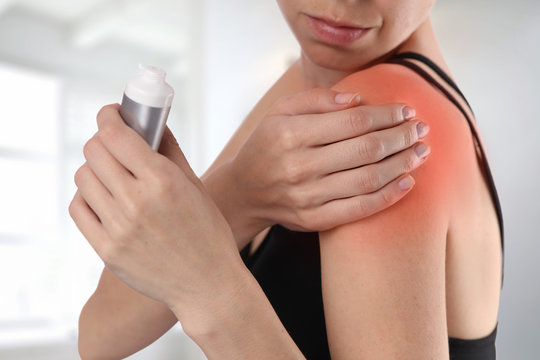 Woman suffering from shoulder back pain applying pain relief cream . Sports exercising injury.