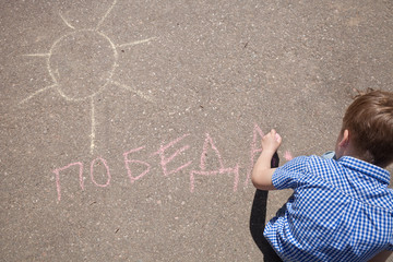 "Top view on kid boy drawing and writing word ""Victory"" in Russian on asphalt. May 9th. Victory day in Russia. Peace in the world. Memorial day"