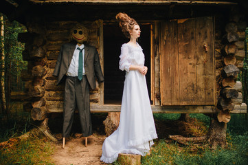 Young beautiful skinny bride girl in vintage wedding dress and hairstyle standing beyond old wooden house in forest with scarecrow from fairytale. Classical russian fable concept and idea. Sorcery.