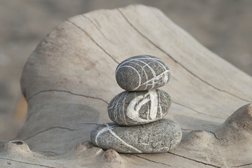 Fototapeta Stack of three stripy pebbles on a driftwood log obraz