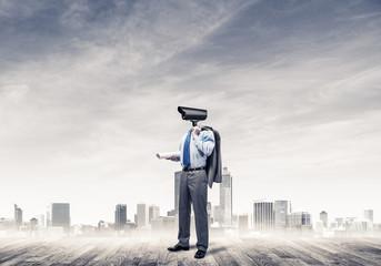 Camera headed man standing on wooden floor against modern citysc
