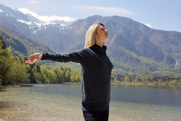 Stress relief activities. Freedom concept. Woman Breathing fresh air and enjoying beautiful mountain lake landscape. Take a break, relax, dream ,smile