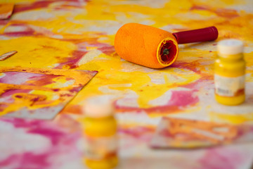 A closeup of artistic instruments, paints, paint roller and paper. The concept of creativity and fantasy development.