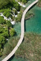 Wooden boardwalk passage in Plitvice National Park. Aerial view. Vivid turquoise lake.