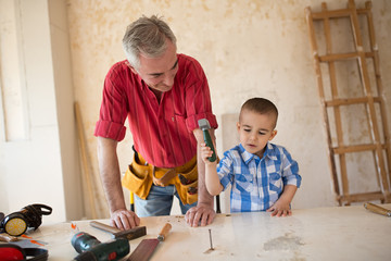 Grandson is helping grandfather in  a carpenter's workshop