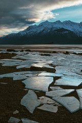 Large Shimmering and Colorful Broken Ice on Mountainous Alaska Beach at Sunset