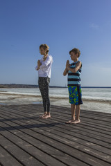 Young woman and boy make a sun salutation with folded palms near the heart, calm and relaxation