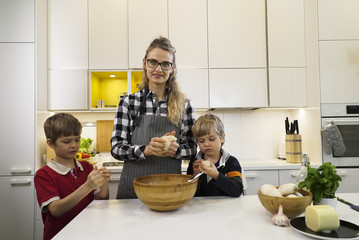 Mother and two kids kneeding dough for pizza or bread in the kitchen