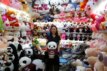 A staff member holds a Panda soft toy as she poses for a picture in a stall at the Yiwu Wholesale Market in Yiwu