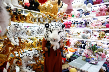 A staff member holds up a toy tiger head as she poses for a picture in a stall at the Yiwu Wholesale Market in Yiwu