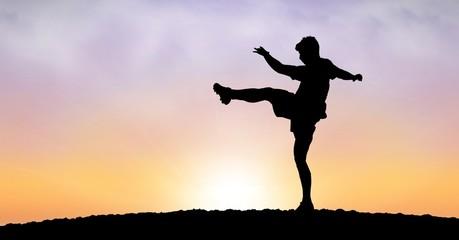Silhouette man exercising against sky during sunset