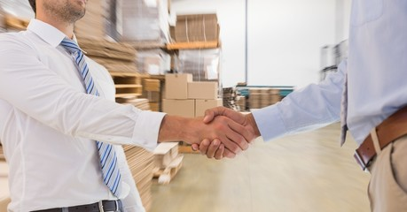 Midsection of businessmen doing handshake in warehouse