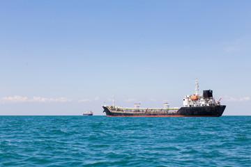 Oil logistic transportation ship over ocean skyline background