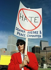 Jane Covode holds an anti-hate sign while attending a rally with the Denver skyline in the backgroun..