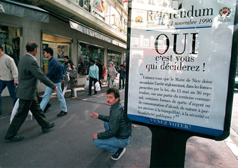 "A homeless man kneels as he begs for money near a poster which reads ""Referendum,YES, it is you who .."