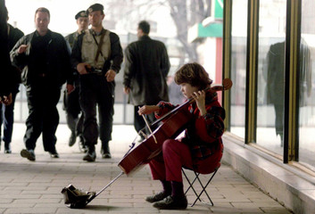 A young girl plays a cello to earn some money as militiamen, armed with machine guns, patrol the str..