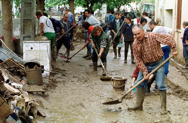 Residents and volonteers shovel mud and debris away after torrential rains sent a river of mud to en..