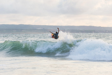 Surfer with a tanned body performs a trick on a short board - a jump over the waves.