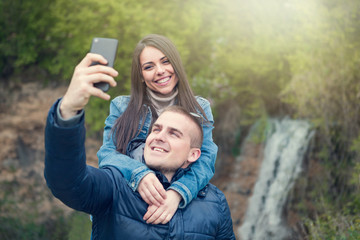Couple taking selfie with smartphone in the nature in spring