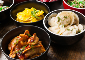 Set of different dumplings and ravioli on a wooden table