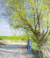 A man with a camera stands under a green tree by the road in summer