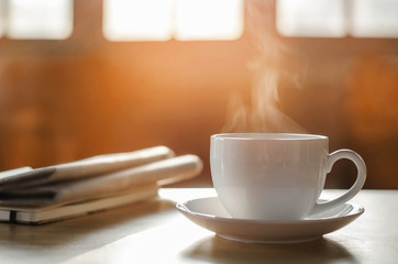 coffee cup with newspaper on the table, coffee shop background, warm tone