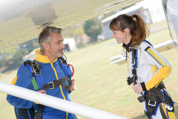 Male and female parachutists under wing of aircraft