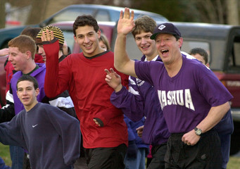 GORE WAVES AS HE JOGS WITH HIGH SCHOOL STUDENTS.