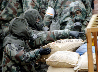 Police dressed in military gasmasks and chemical resistant suits load bags of sodium flouride, one o..