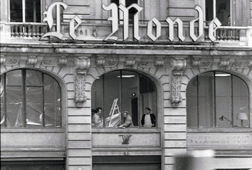 Workers clean the debris at Le Monde newspaper headquarters after a bomb explosion at the Israeli Leumi bank in Paris