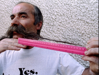 Manol Manolov, 51, poses for a picture as he shows off his 66cm long moustache at his home in Sofia,..