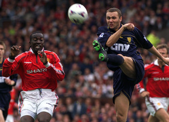 WIMBLEDON'S DEAN BLACKWELL CLEARS THE BALL FROM DWIGHT YORKE OF MANCHESTER UNITED.