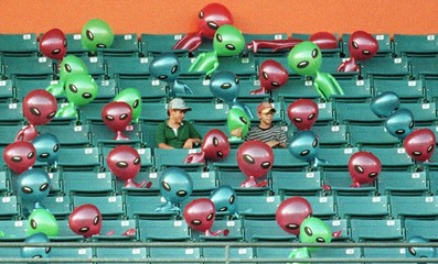 MARLINS FANS WATCH GAME SURROUNDED BY ALIEN BLOW UP DOLLS.