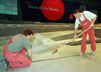 """Two workers lay down a carpet in front of a logo reading """"the new power"""" for the opposition social d.."""