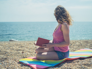 Young woman sitting on beach reading a book in summer