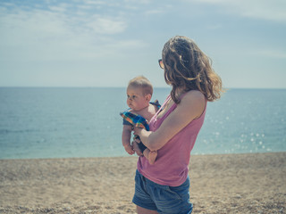 Mother standing on beach with baby