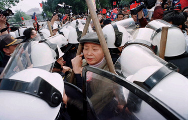 An elder protestor is surrounded   riot-police after he tried to get in the Taiwan ruling Nationalis..