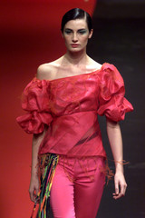 A model for French designer Christian Lacroix presents this off-the-shoulder blouse with short ruffl..