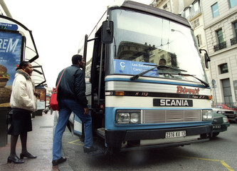 Passengers speak with a driver of one of the few private buses chartered by the city to run a skelet..