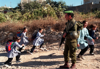 Palestinian school girls scurry past an armed Israeli infantry soldier as they return home from scho..