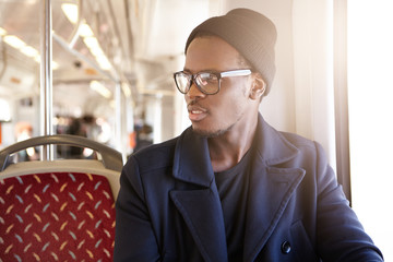 Pensive African man wearing black hat, eyeglasses and coat sitting near window in public transport, looking aside with thoughtful face expression, thinking about forthcoming interview with employer