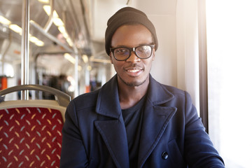 Young happy and handsome dark-skinned hipster looking at camera with cheerful smile, dressed in trendy clothes, getting to work by bus. People, lifestyle, travel, transportation and public transport