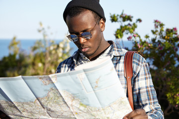 Serious lost European black student in stylish clothing standing against blue sea and green trees background, having worried look, trying to find right way on paper guide after his mobile run down