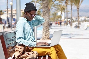 Stylish young African American male freelancer wearing hat and shades using laptop for remote work, using free city wireless internet connection, sitting alone on bench on promenade by the sea