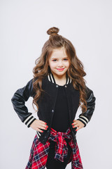 portrait of little modern model in studio. Curly hairstyle, fashion clothes